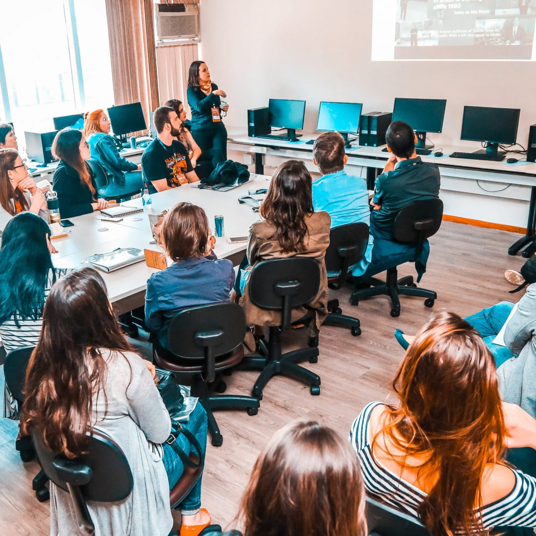 #PraCegoVer #PraTodesVerem: A foto mostra diversas pessoas sentadas em cadeiras assistindo a uma palestra, que está sendo apresentada pela criadora da Otimifica, Ariane Feijó. Ela está de pé, ao lado de uma projeção que está sendo feita na parede.