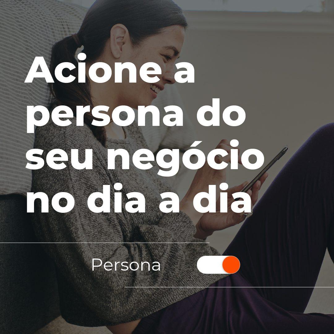 #PraCegoVer: a imagem mostra uma mulher branca sorrindo e mexendo no celular enquanto está sentada no chão, apoiando suas costas em uma cama. Em cima da fotografia está escrito: